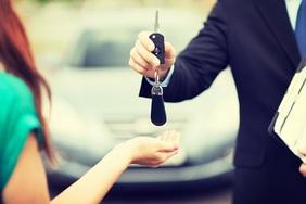 car-salesman-handing-keys-to-female-driver-teaser